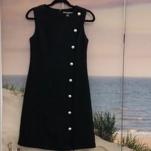 Long sleeve less black dress with  pearl buttons.